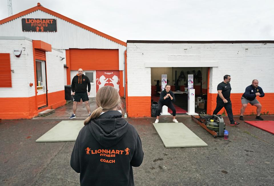 People take part in a small exercise class at the Lionheart Fitness gym in Bedlington, Northumberland, which moved some equipment into the car park during lockdown. (PA)