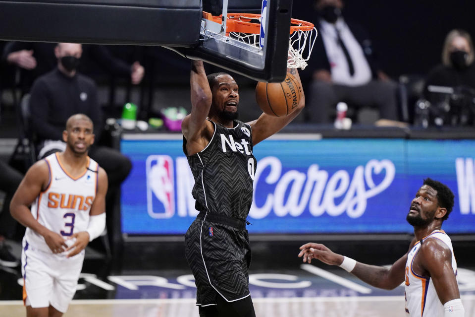 Phoenix Suns guard Chris Paul, left, and Suns center Deandre Ayton, right, watch as Brooklyn Nets forward Kevin Durant (7) dunks unopposed the third quarter of an NBA basketball game, Sunday, April 25, 2021, in New York. (AP Photo/Kathy Willens)