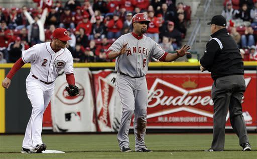 Los Angeles Angels first baseman Albert Pujols (5) questions second base umpire Todd Tichenor over a call after Cincinnati Reds shortstop Zack Cozart (2) tagged Pujols out trying to steal second in the first inning of a baseball game, Wednesday, April 3, 2013, in Cincinnati. (AP Photo/Al Behrman)