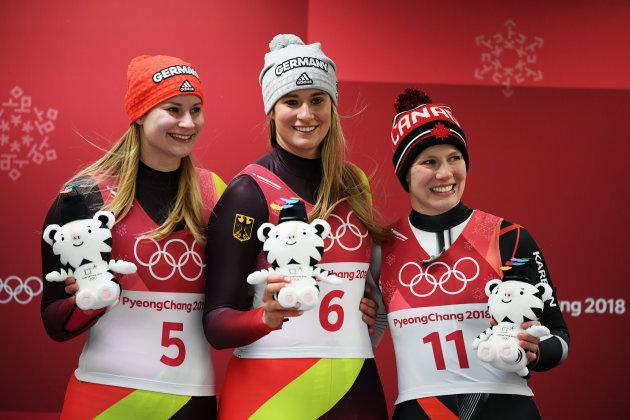 Silver medalist Dajana Eitberger of Germany, left, gold medalist Natalie Geisenberger of Germany, middle, and bronze medalist Alex Gough of Canada celebrate following the women's luge final.
