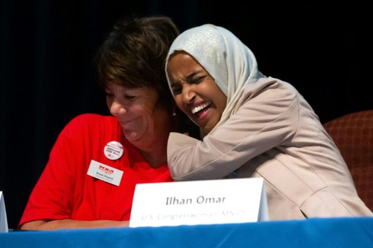 "US Representative Ilhan Omar(R) hugs Rose Roach, Executive Director of the Minnesota Nurses Association, at a ""Medicare for All"" town hall meeting in Minneapolis, after Omar returned home following attacks by President Donald Trump"