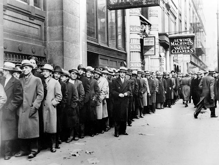 In this Nov. 24, 1933 file photo, unemployed men wait outside the State Labor Bureau in New York. The epic hardship of the 1930s is the best-known depression in American history, and some economists are concerned the repercussions of the COVID-19 crisis could send the U.S. reeling back to those difficult times.