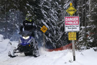 A snowmobile rider checks for traffic before crossing a road on a trail near Rangeley Lake, Saturday, Jan. 23, 2021, in Rangeley, Maine. Warmer-than-usual temperatures and scant snowfall led to a slow start to the riding season in Maine. (AP Photo/Robert F. Bukaty)