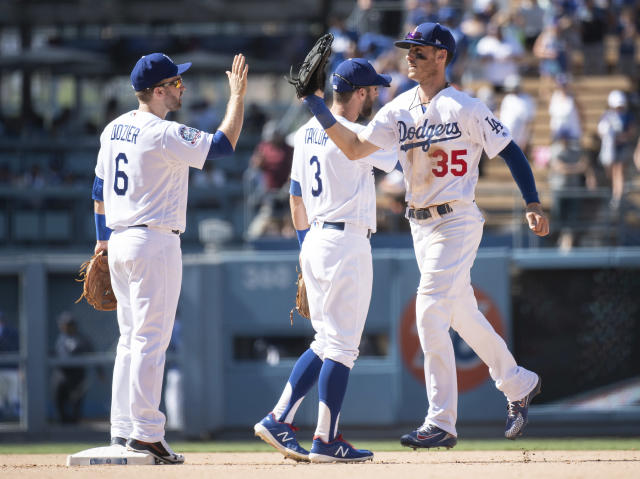 Los Angeles Dodgers second baseman Brian Dozier, left, and center fielder Cody Bellinger celebrate their win over the Houston Astros in a baseball game in Los Angeles, Sunday, Aug. 5, 2018. (AP Photo/Kyusung Gong)