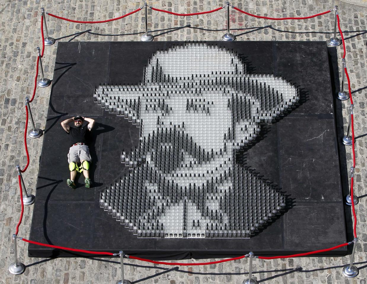 "Artist Herb Williams, of Nashville, Tenn., poses with his Guinness World Record-breaking mosaic, a portrait of ""Mr. Jack"" made from over 2000 empty Jack Daniel's Tennessee Whiskey bottles, during an event celebrating the brand's 161st birthday at South Street Seaport, Thursday, Sept. 1, 2011 in New York. Jack Daniel's celebrated it's 161st birthday by breaking 6 Guinness World Records during the event. (AP Photo/Jack Daniel's, Jason DeCrow)"