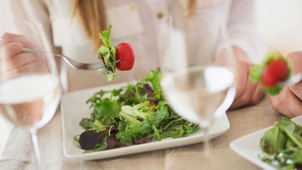 photo a woman eats salad in an undated stock photo stock photo