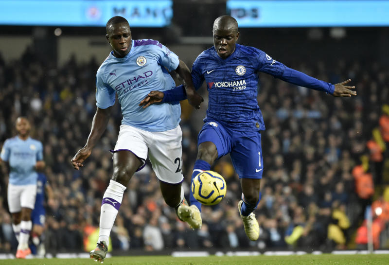 Chelsea's N'Golo Kante, right, controls the ball to shoot and score the opening goal nest to Manchester City's Benjamin Mendy, left, during the English Premier League soccer match between Manchester City and Chelsea at Etihad stadium in Manchester, England, Saturday, Nov. 23, 2019. (AP Photo/Rui Vieira)