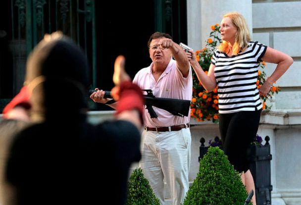 PHOTO: Armed homeowners Mark and Patricia McCloskey, standing in front their house along Portland Place confront protesters marching to St. Louis Mayor Lyda Krewson's house in St. Louis, June 28, 2020.  (Laurie Skrivan/Louis Post-Dispatch via AP, FILE)