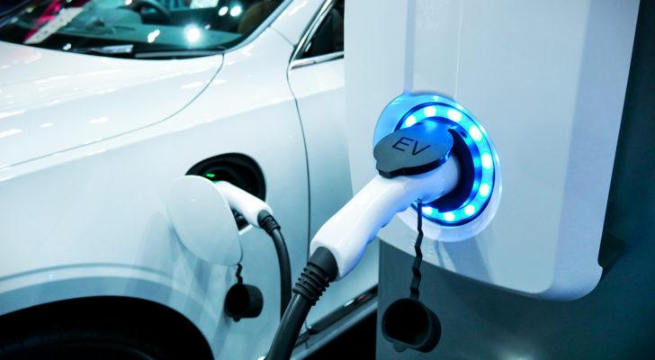 an electric car plugged in for charging, representing electric car stocks
