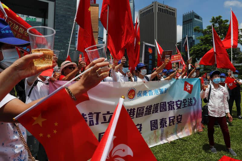 Pro-China supporters celebrate with champagne after China's parliament passes national security law for Hong Kong, in Hong Kong