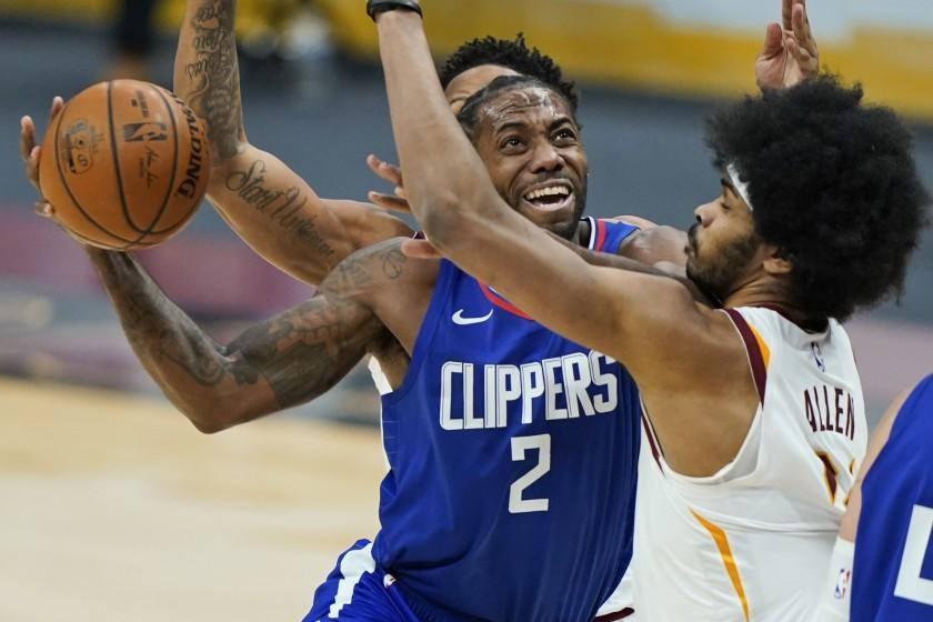 Los Angeles Clippers' Kawhi Leonard (2) drives to the basket against Cleveland Cavaliers' Jarrett Allen (31) during the second half of an NBA basketball game Wednesday, Feb. 3, 2021, in Cleveland. (AP Photo/Tony Dejak)