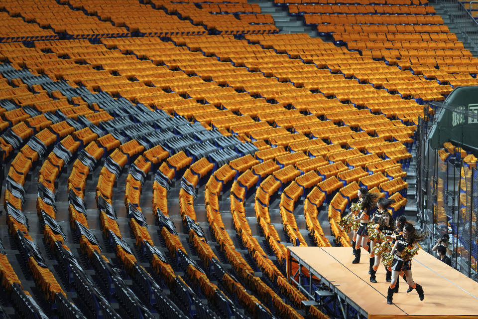 Cheer leaders perform to empty stands prior an opening baseball game between the Yomiuri Giants and the Hanshin Tigers at Tokyo Dome in Tokyo Friday, June 19, 2020. Japan's economy is opening cautiously, with social-distancing restrictions amid the coronavirus pandemic. (AP Photo/Eugene Hoshiko)