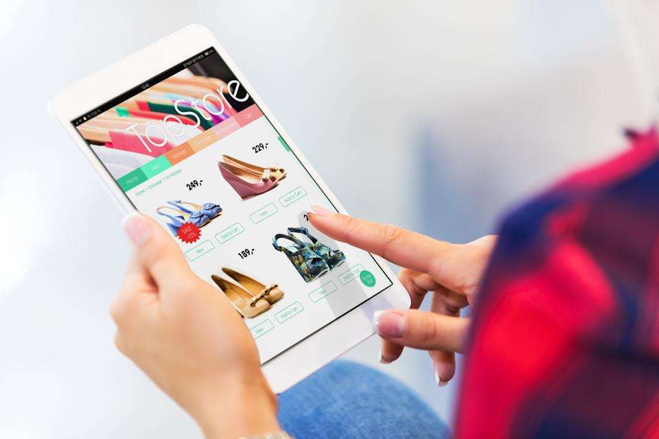 Young woman shopping online with tablet computer and making purchase and payment with selective focus effect