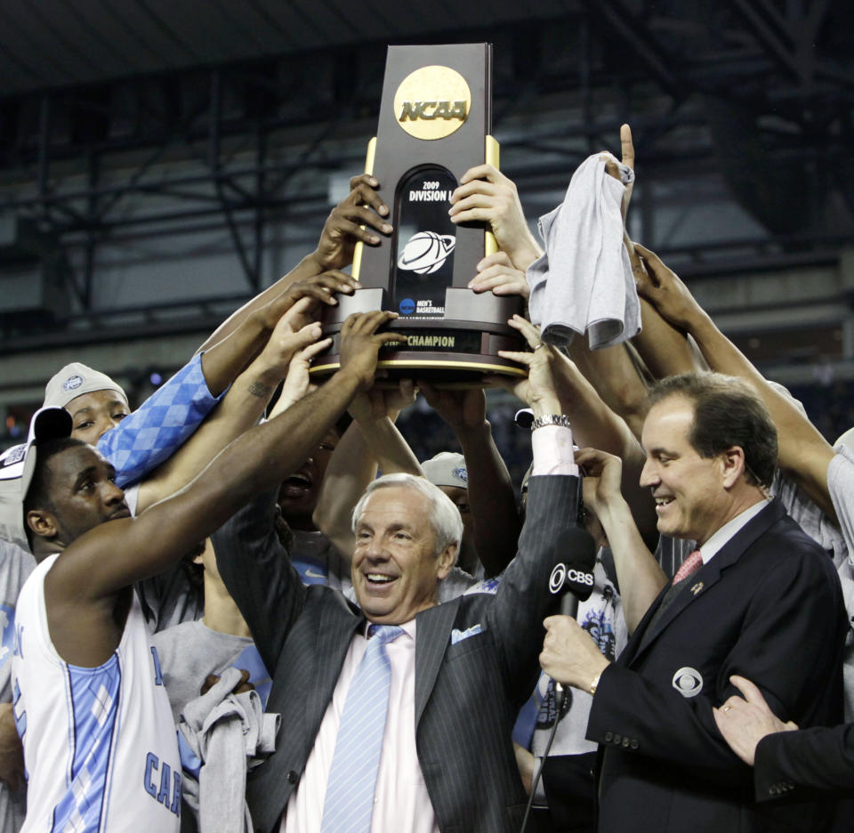 FILE - North Carolina head coach Roy Williams, center, celebrates with his team after their 89-72 victory over Michigan State in the championship game at the men's NCAA Final Four college basketball tournament in Detroit, in this Tuesday, April 7, 2009, file phto. North Carolina announced Thursday, April 1, 2021, that Hall of Fame basketball coach Roy Williams is retiring after a 33-year career that includes three national championships. (AP Photo/Paul Sancya, File)