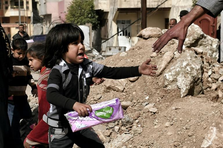 An Iraqi girl is helped by a man during aid distribution in western Mosul