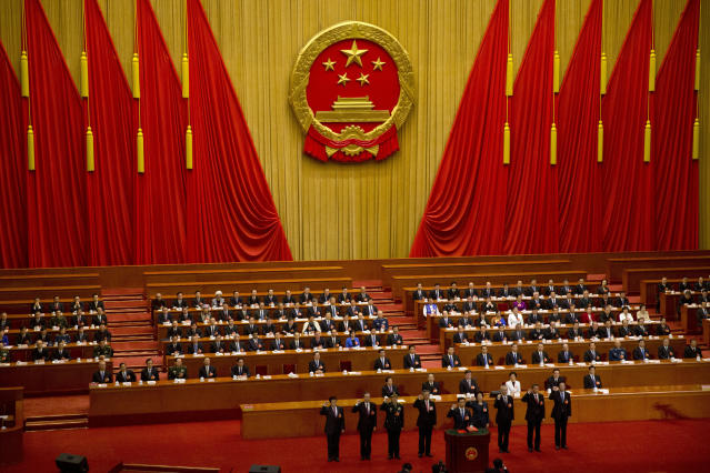 FILE - In this March 19, 2018, file photo, newly-appointed officials take the oath of office during a plenary session of China's National People's Congress (NPC) at the Great Hall of the People in Beijing. A new defense intelligence assessment lays out U.S. concerns about China's growing military might, underscoring worries that Beijing could decide it has the ability to attack Taiwan and win. (AP Photo/Mark Schiefelbein, File)