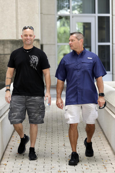 In this Thursday, Sept. 12, 2019, photo, Eric Reynolds, left, and Dave Stull, both police officers, get together in Orlando, Fla. They recently found out they were half brothers though a DNA test. (AP Photo/John Raoux)