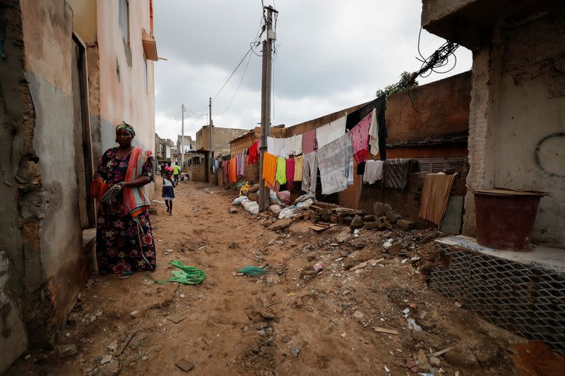 A woman stands near a wall damaged by the flood after heavy rains in Cayor on the outskirts of Dakar