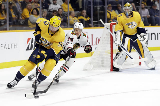 Nashville Predators defenseman Matt Irwin (52) and Chicago Blackhawks center David Kampf (64), of the Czech Republic, compete for the puck during the first period of an NHL hockey game Tuesday, Oct. 29, 2019, in Nashville, Tenn. (AP Photo/Mark Humphrey)