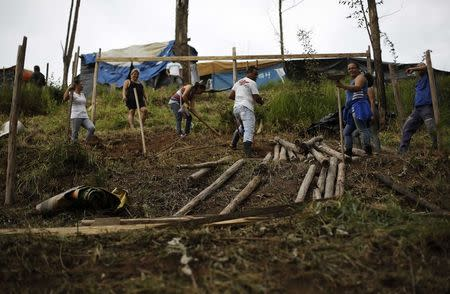 "A family of MTST work on a newly built shack at the ""People's World Cup"" camp in Sao Paulo"
