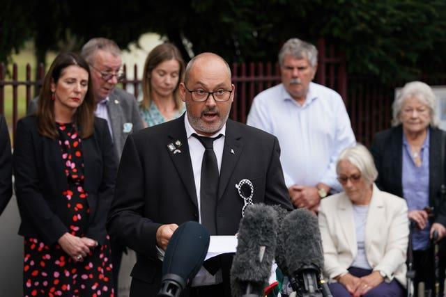 Stuart Stephens, the father of Olly Stephens, reads a statement outside Reading Crown Court beside his mother Amanda