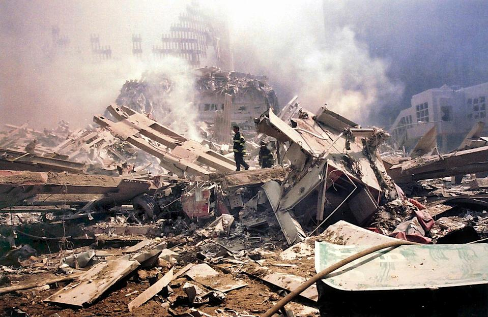 <p>Firemen walk amid the smouldering rubble of the World Trade Center. (AP)</p>
