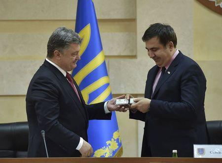Ukrainian President Poroshenko hands over identification card to Saakashvili as governor of Odessa region during his introduction in Odessa