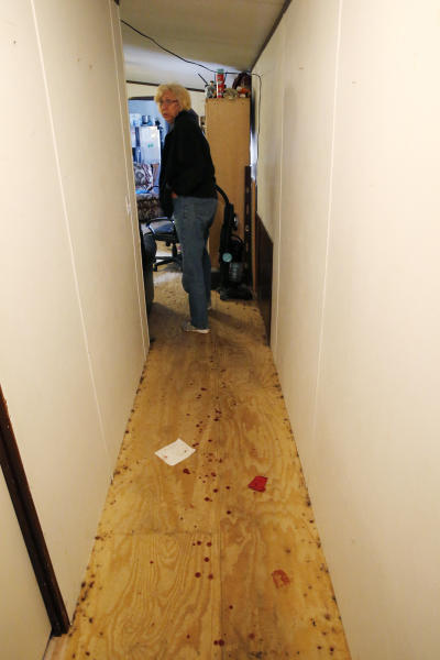 EDS NOTE: GRAPHIC CONTENT - Kim Mincks walks down a blood stained hallway inside her home in Gonzalez, La., Sunday, Jan. 27, 2019, where two of her housemates, Keith Theriot and his wife Elizabeth Theriot, were killed in another room yesterday while she slept. (AP Photo/Gerald Herbert)