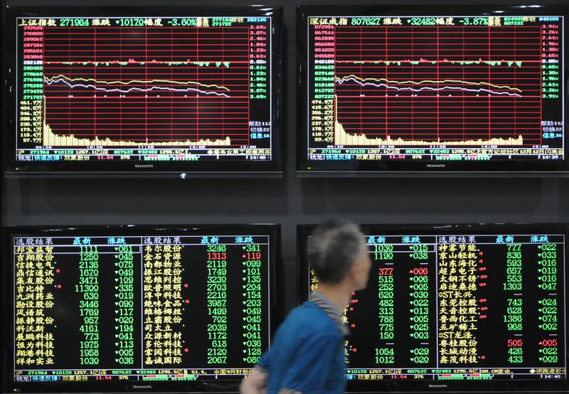 Man walks past screens showing stock information at a brokerage house in Jiujiang