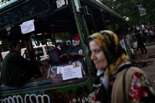 Demonstrators sit inside a destroyed bus at Taksim Square in Istanbul on June 6, 2013