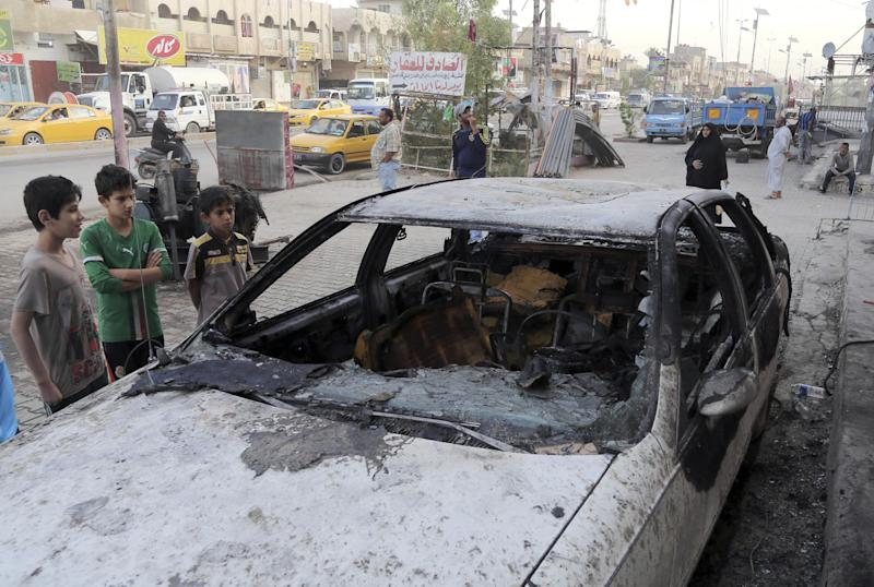 Civilians inspect a damaged vehicle in the aftermath of a Monday car bomb attack in a crowded commercial street in Baghdad's eastern neighborhood of Sadr City, Iraq, Tuesday, April 22, 2014. Suicide bombings and other attacks across Iraq killed and wounded dozens on Monday, officials said, the latest in an uptick in violence as the country counts down to crucial parliamentary elections later this month. (AP Photo/Karim Kadim)