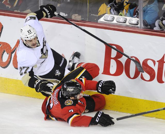 Pittsburgh Penguins' Craig Adams, top, falls over Calgary Flames' TJ Brodie during the second period of an NHL hockey game in Calgary, Alberta, Saturday, Jan. 11, 2014. (AP Photo/The Canadian Press, Larry MacDougal)