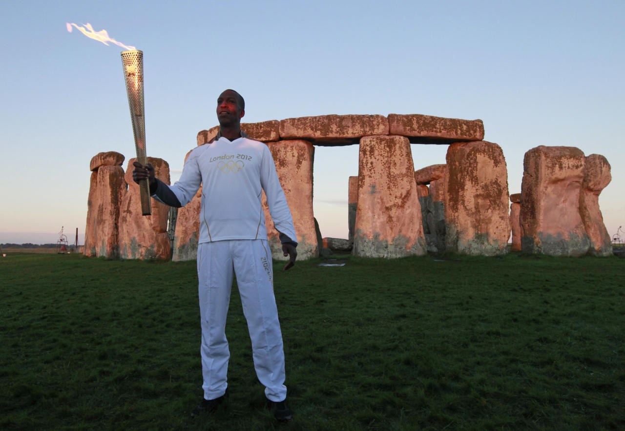 U.S. Olympian sprinter Michael Johnson poses for the photographers holding the Olympic Flame at Stonehenge, England, Thursday, July 12, 2012. Johnson, who won four Olympic gold medals and eight world championship gold medals, currently holds the world and Olympic records in the 400 meters and 4 x 400 meters relay. The Olympic Torch is being carried around England in a relay of torchbearers to make its way to the London 2012 Olympic Games opening ceremony. (AP Photo/Lefteris Pitarakis)
