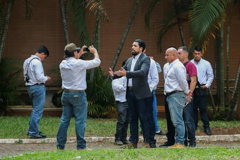 Supporters of Venezuela's opposition leader Juan Guaido record a video from the grounds of the Venezuelan embassy in Brasilia