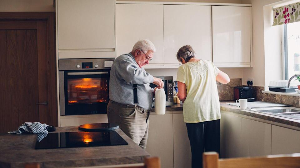 Elderly couple working in the kitchen together.