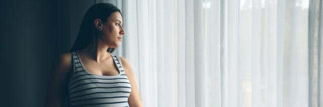 A pregnant woman standing by a window covered in white curtains