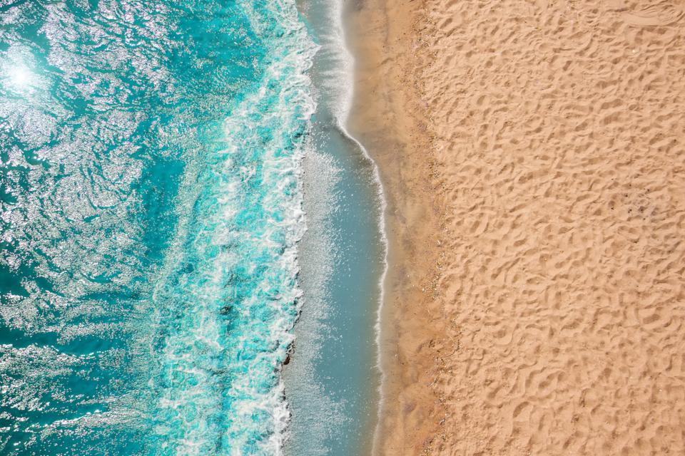 Coastline Beach Ocean waves with foam on the sand. Top view from drone