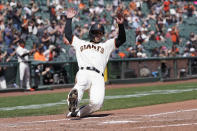 San Francisco Giants' Tommy La Stella slides home to score against the Colorado Rockies during the third inning of a baseball game in San Francisco, Saturday, April 10, 2021. (AP Photo/Jeff Chiu)