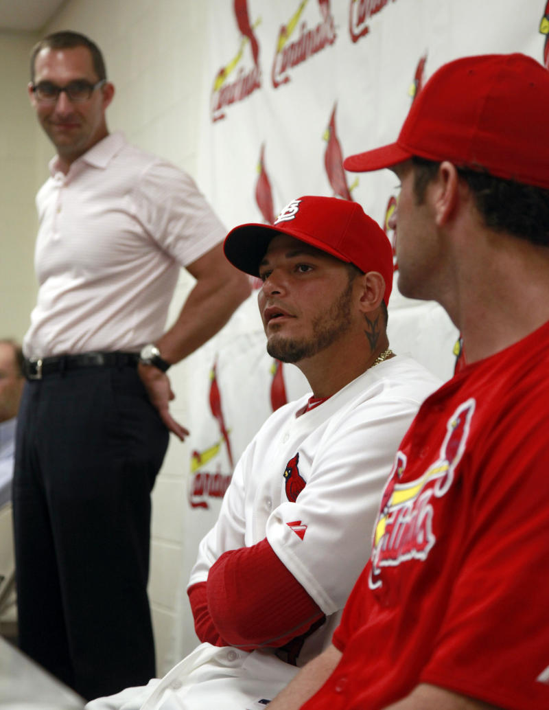 St. Louis Cardinals catcher Yadier Molina, center, speaks as Cardinals general manager John Mozeliak, left, and manager Mike Matheny listen during news conference at spring training announcing the singing of Molina to a new five-year contract, Thursday, March 1, 2012, in Jupiter, Fla. The new contract keeps Molina with the Cardinals through the 2017 season with a mutual option for 2018.  (AP Photo/Jeff Roberson)