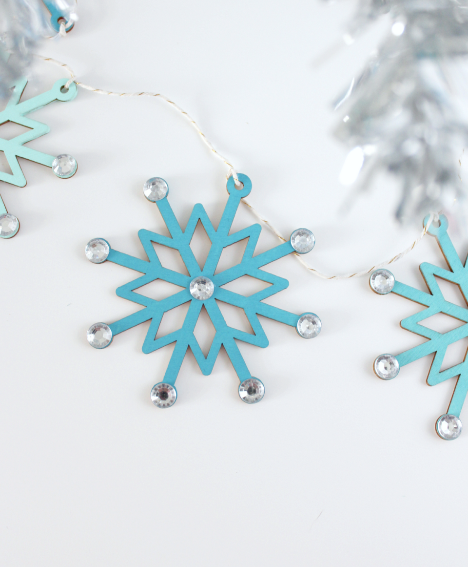 """<p>Make wooden snowflake figures stand out with varying shades of blue and rhinestone embellishments. </p><p><a href=""""https://www.whitehousecrafts.net/post/2019/11/13/sparkly-snowflake-garland"""" rel=""""nofollow noopener"""" target=""""_blank"""" data-ylk=""""slk:Get the tutorial."""" class=""""link rapid-noclick-resp"""">Get the tutorial.</a></p><p><a class=""""link rapid-noclick-resp"""" href=""""https://www.amazon.com/TecUnite-Crystal-Rhinestones-Tweezer-Picking/dp/B07D3Q1FKJ?tag=syn-yahoo-20&ascsubtag=%5Bartid%7C10072.g.37499128%5Bsrc%7Cyahoo-us"""" rel=""""nofollow noopener"""" target=""""_blank"""" data-ylk=""""slk:SHOP RHINESTONES"""">SHOP RHINESTONES</a></p>"""