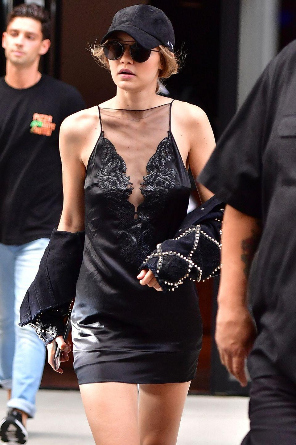 <p>Hadid wears a paneled silk slip dress, embellished jacket slung at her arms, black baseball cap and aviator sunglasses while out with Kendall Jenner in New York. </p>