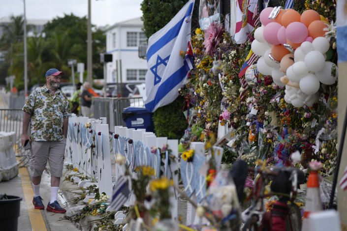 Peter Martin, of New York, who was in Miami visiting his brother, pays his respects at a makeshift memorial for the victims of the Champlain Towers South building collapse, on Monday, July 12, 2021, in Surfside, Fla. (AP Photo/Rebecca Blackwell)