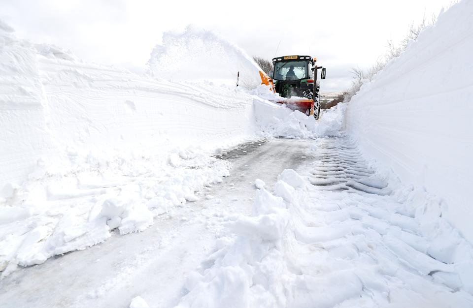 """A farmer in a tractor helps to clear the snow from a blocked road heading out of Simonsbath in Exmoor National park, as the icy conditions brought by the """"Mini Beast from the East"""" are set to cling on for one more day before Britain will see the return of spring."""