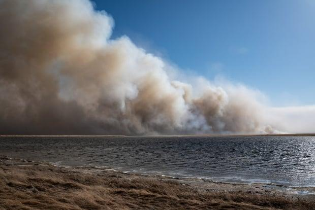 Smoke from the grass fire billowed in the air east of Claresholm, Alta., on Sunday afternoon.