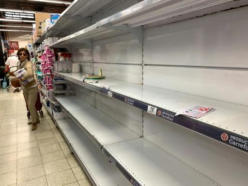 A woman in Argentina walks next to shelves emptied due to fears of the new coronavirus