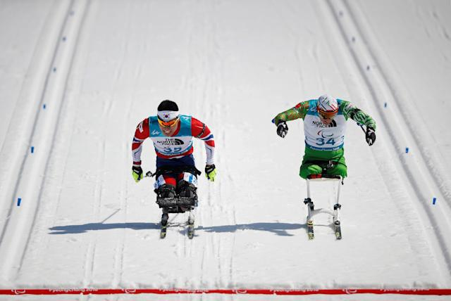 Biathlon - Pyeongchang 2018 Winter Paralympics - Men's 12.5km - Sitting - Alpensia Biathlon Centre - Pyeongchang, South Korea - March 13, 2018 - Sin Eui-hyun (L) of South Korea and Dzmitry Loban of Belarus race to cross the finish line. REUTERS/Carl Recine