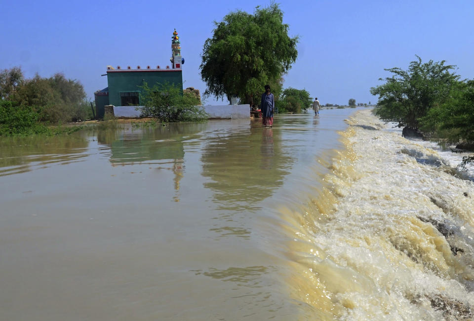 Villagers wade through a flooded area of Dadu, a district in Pakistan's southern Sindh province, Sunday, Aug. 9, 2020. Pakistan's disaster management agency said three days of heavy monsoon rains that triggered flash floods have killed dozens of people in various parts of the country. (AP Photo/Pervez Masih)