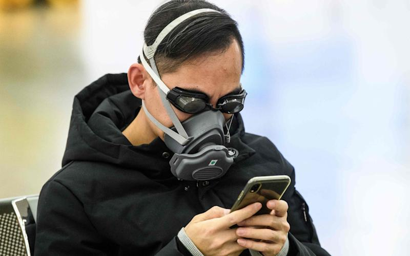 A traveller wears protective gear waiting for the high speed train between Hong Kong and China - AFP