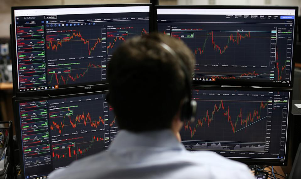 Employees monitor financial data on their computer screens as they work the brokerage ActivTrades in London on March 15, 2019. (Photo: ISABEL INFANTES/AFP via Getty Images)