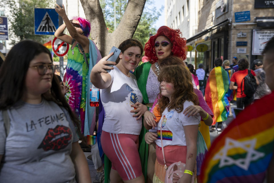 Participants stop for a photo in the annual Gay Pride parade in Jerusalem, Thursday, June 3, 2021. Thousands of people marched through the streets of Jerusalem on Thursday in the city's annual gay pride parade. (AP Photo/Ariel Schalit)